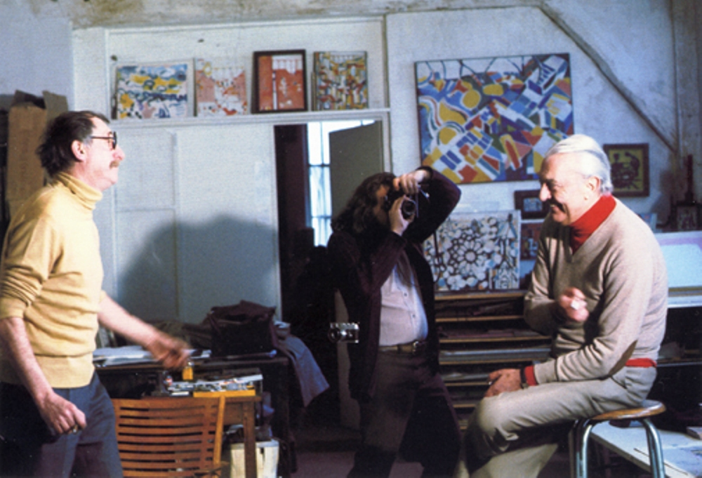 Jacques Lagrange and Jacques Tati, with artworks by the former in the background